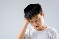 Boy headache. Young asian boy feel unhappy because of headache on white background royalty free stock image