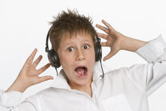 Boy with Headphones. Shocked and startled by loud noise. Shot in studio on white background Royalty Free Stock Images