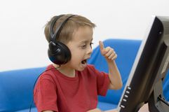 Boy with headphones. On is looking at the computer screen with excited expression and thumbs up. Soft focus on the face Royalty Free Stock Photos