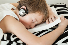 Boy with headphones asleep on top of textbook. Exhausted young male student in undershirt with headphones asleep on top of textbook over striped black and white Royalty Free Stock Image