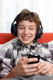 Boy with Headphones Listening to mp3 player. A preteen boy having fun as he listens to his mp3 player through big headphones on his head. He's seated on an Stock Image
