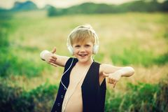 Boy with headphones listening to music in nature. Emotional boy with headphones listening to music in nature Stock Image