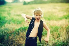 Boy with headphones listening to music in nature. Emotional boy with headphones listening to music in nature Royalty Free Stock Photos