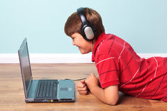 Boy with headphones looking at laptop Royalty Free Stock Photo