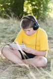 Boy in headphones looking tablet computer on the Stock Photos