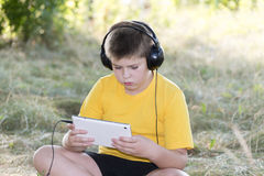 Boy in headphones looking tablet computer on the Royalty Free Stock Image