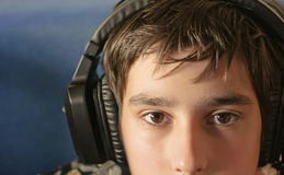 Boy with headphones. Looks at the camera during playing computer games, chatting on the internat, watching a video or listening to music Stock Photos