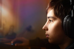 Boy with headphones. Looks at a computer monitor Royalty Free Stock Images