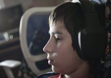 Boy with headphones. Looks in the monitor during playing computer games Royalty Free Stock Image