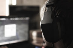 Boy with headphones. Looks in the monitor during playing computer games, chatting on the internat, watching a video or listening to music Stock Images