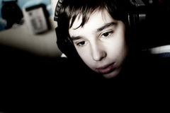 Boy with headphones. Looks in the monitor during playing computer games, chatting on the internat, watching a video or listening to music Royalty Free Stock Images