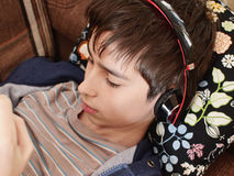 Boy with headphones. Looks on the tablet Royalty Free Stock Photo