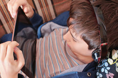 Boy with headphones looks on the tablet Stock Photo