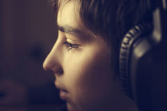 Boy with headphones. During playing computer games, chatting on the internat, watching a video or listening to music Stock Photos