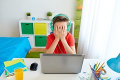 Boy in headphones playing video game on laptop stock photo