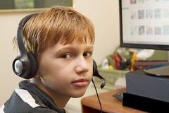 Boy with Headphones on Playing Video Games Royalty Free Stock Image