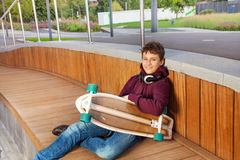 Boy with headphones relaxes and holds skateboard Stock Image