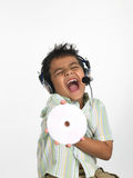 Boy with headphones shouting. Asian boy with headphones holding cd shouting Royalty Free Stock Photos