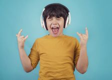 Boy with headphones showing rock sigh. On blue background Stock Photo