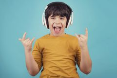 Boy with headphones showing rock sigh. On blue background Royalty Free Stock Photos