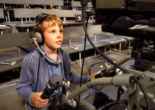 Boy with headphones sits on video camera Royalty Free Stock Photos
