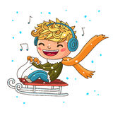 Boy with headphones sledding in the winter Royalty Free Stock Photo