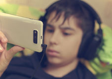 Boy with headphones and smart phone. Boy with headphones using a smart phone to listen music, chatting on the internat, watching a video or reading Royalty Free Stock Photos