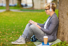 Boy with headphones, tablet pc, books and coffee Royalty Free Stock Photos
