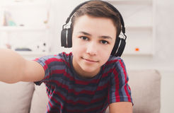 Boy in headphones taking selfie at home. Teenager taking selfie in headphones on phone while listen to music. Shot of teenage kid on couch at home Stock Photos
