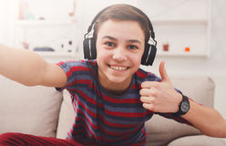 Boy in headphones taking selfie, like gesture. Teenager taking thumb up selfie in headphones on phone while listen to music. Shot of teenage kid gesturing with Stock Images