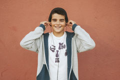 Boy with headphones. Urban boy with headphones on the wall Royalty Free Stock Photo