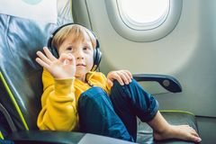 Boy with headphones watching and listening to in flight entertainment on board airplane royalty free stock images