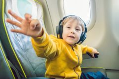 Boy with headphones watching and listening to in flight entertai. Nment on board airplane Royalty Free Stock Images