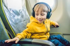 Boy with headphones watching and listening to in flight entertai. Nment on board airplane Stock Photography