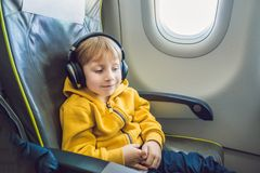 Boy with headphones watching and listening to in flight entertainment on board airplane.  stock photos