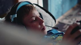 A boy with a headset on his head in a video game lying on the couch. He`s holding a controller. Fun at home. Good mood. Rest. Children stock footage