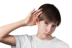 Boy hearing something isolated on white. Boy hearing something enclosing his hand to his ear isolated on white Royalty Free Stock Image