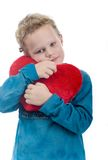 Boy with heart shaped cushion. Cute young boy cuddling red heart shaped cushion or pillow; white studio background Royalty Free Stock Photography