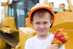 Boy in a helmet. Boy in helmet is against the background of a large excavator Stock Images