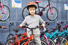 Boy in helmet chooses with bicycle in sport shop Royalty Free Stock Images