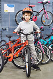 Boy in helmet chooses with bicycle in sport shop Royalty Free Stock Photo