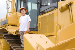Boy in a helmet is a large excavator Royalty Free Stock Photo