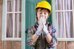 Boy in helmet looking at hands in protective gloves Royalty Free Stock Image