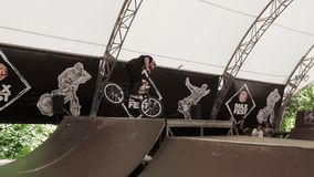Boy in helmet make extreme trick on BMX bicycle inside skate park. Slow motion stock footage