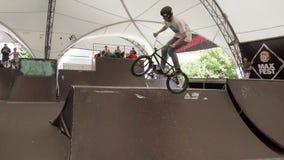 Boy in helmet make tricks on BMX bicycle inside skate park. Audience Slow motion stock video