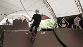 Boy in helmet make very extreme jump on BMX bicycle in skate park. Slow motion stock video