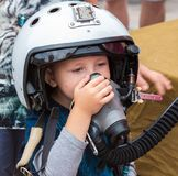 Boy in helmet pilot on annual military exhibition Russian Army 2018 on Central Uglovoe Aerodrome. stock photography
