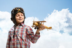 Boy in helmet pilot playing with a toy airplane Stock Images