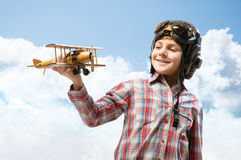 Boy in helmet pilot playing with a toy airplane Royalty Free Stock Images