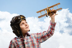 Boy in helmet pilot playing with a toy airplane Stock Photo